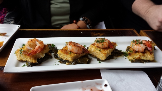 Hers - Shrimp served atop cheddar grit cakes and greens
